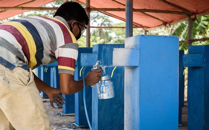 (person's name) paints 1 of the 3,000 OHorizons' water filters that will end up in Bangladeshi families homes in 2017 alone.  That's safe and easy water access for 15,000 people!