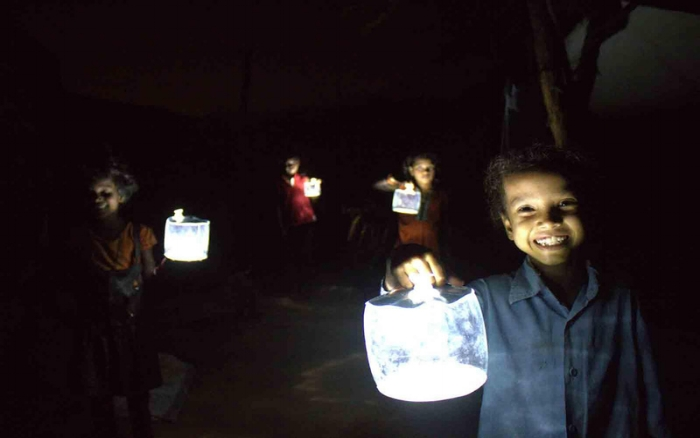 Children show off the illuminating power of the portable inflatable solar lights we're distributing.