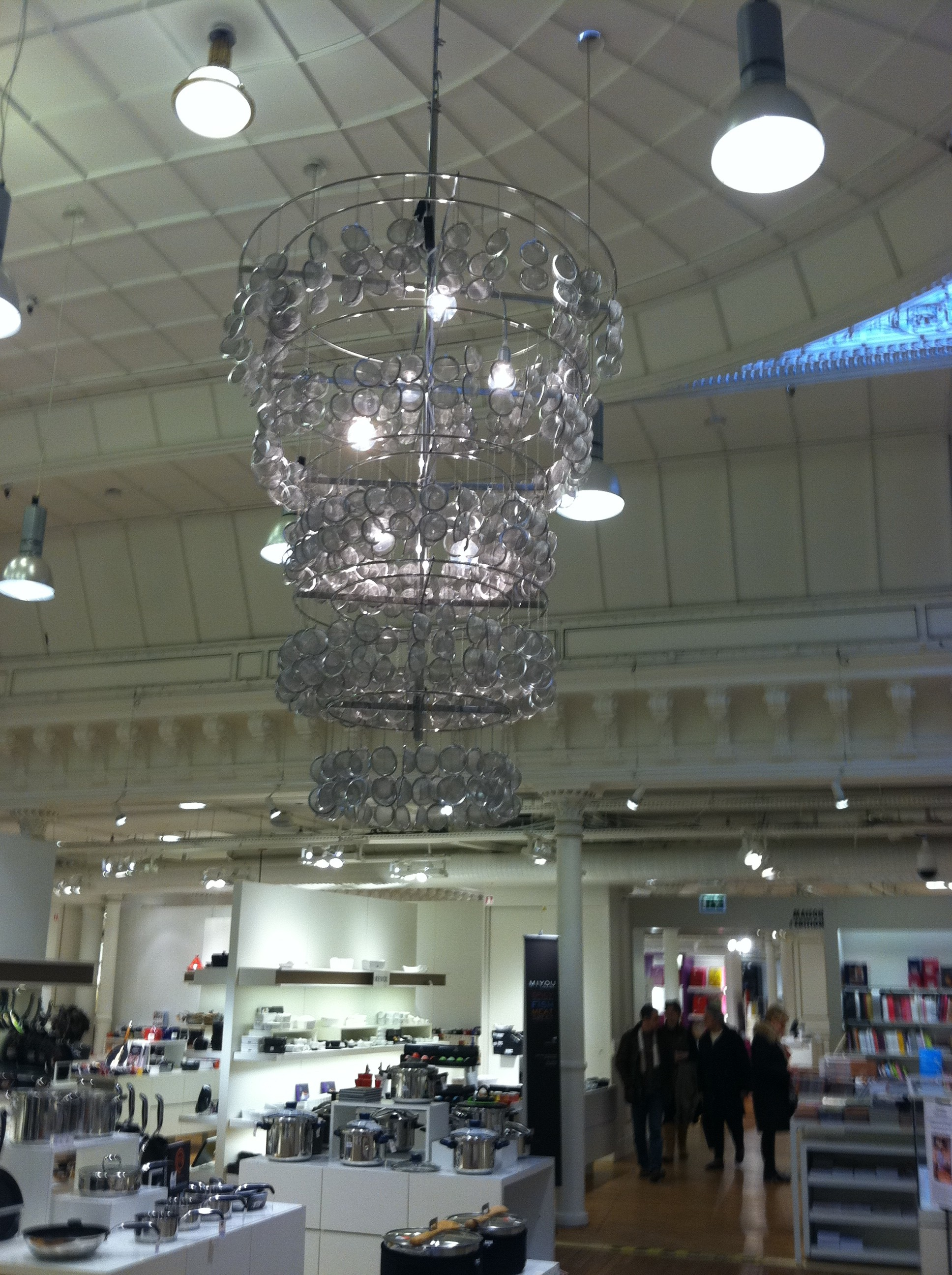A large chandelier made up of repurposed strainers