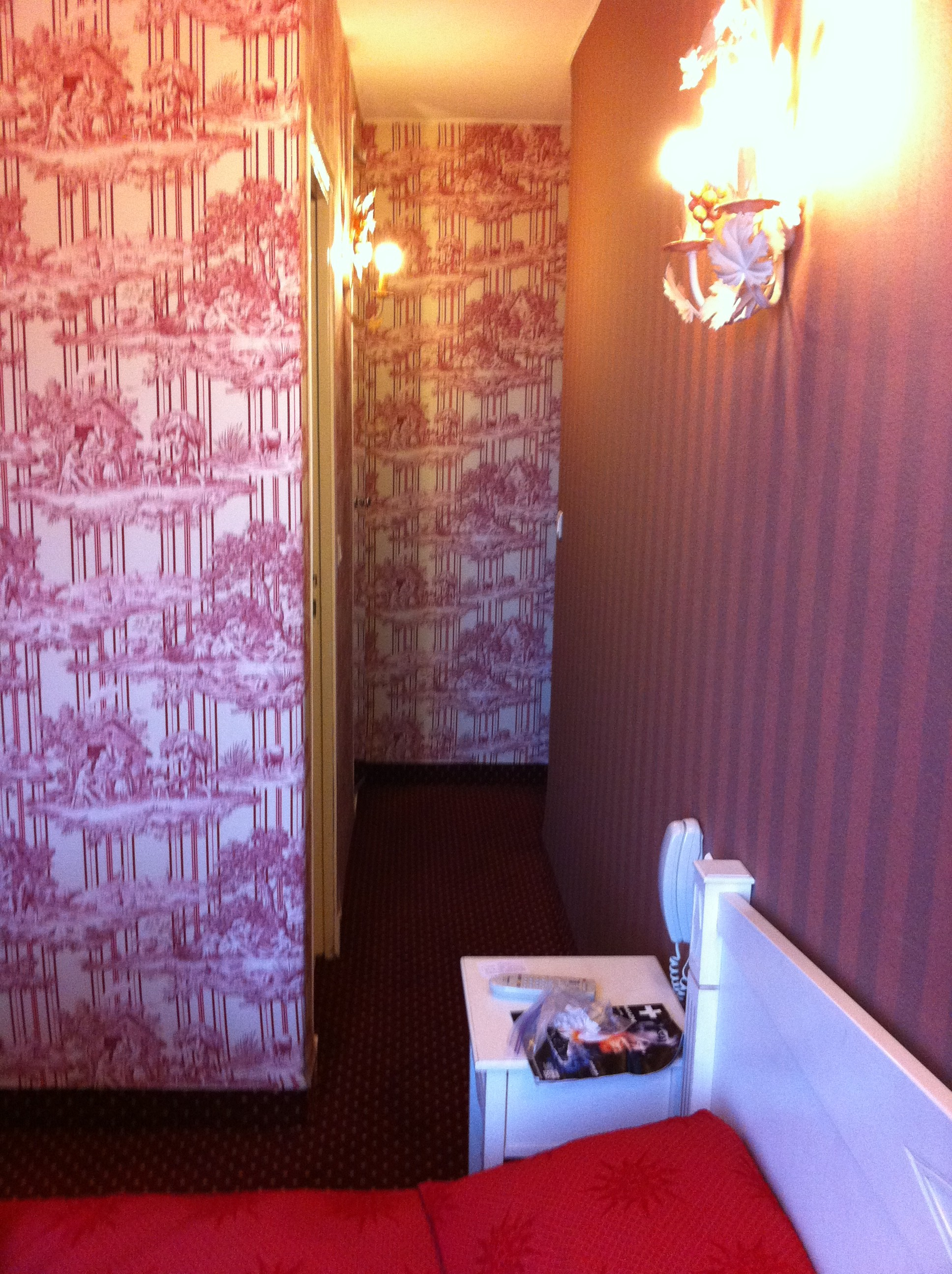 Interior shot of toile upholstered walls inside Paris hotel room