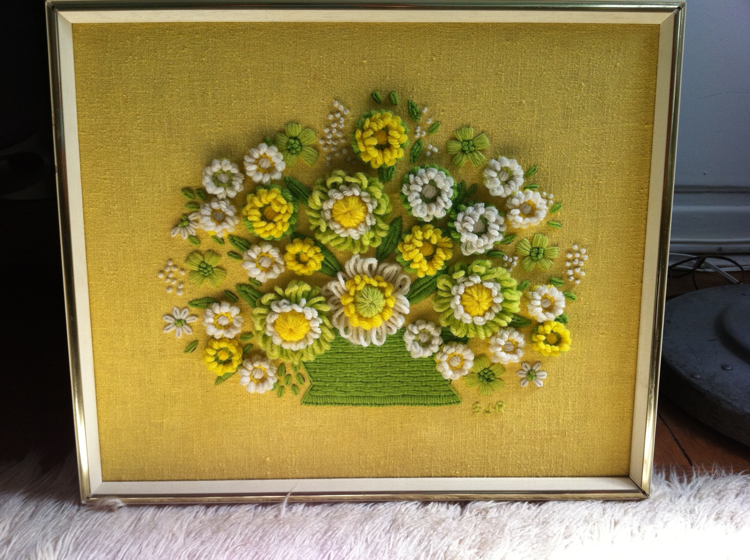 A wonderfully happy green and yellow yarn art bouquet atop a yellow linen background