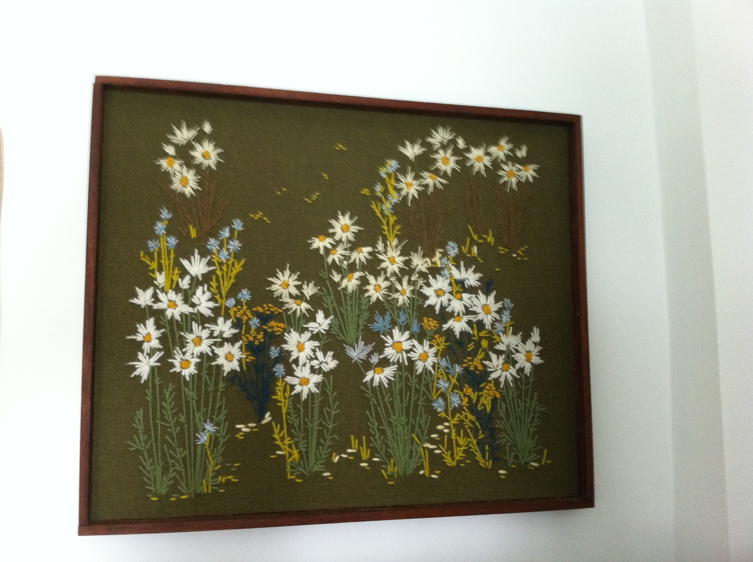 A pic of yarn art featuring daisies on olive green linen background framed in teak.