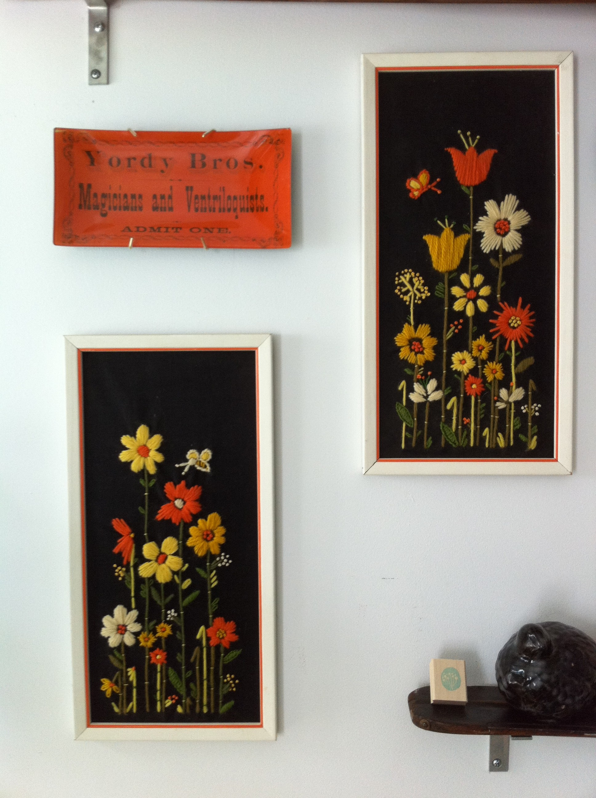 Yellow and orange flowered yarn art on black backgrounds in PJ Mehaffey's apt