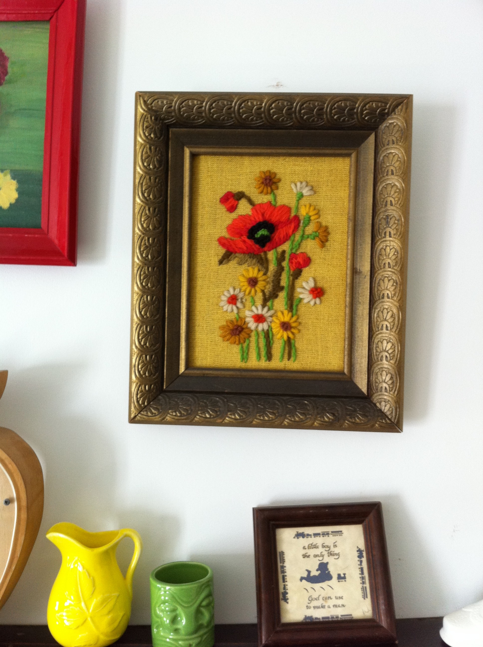 A pic of yarn artwork featuring a large red flower on a yellow linen background in a gold frame