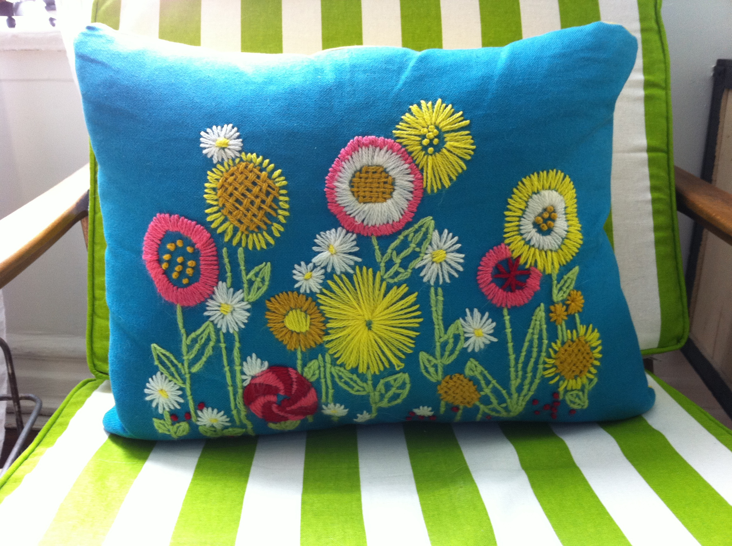 Amazing pink, yellow and red floral yarn art pillow on a green striped chair