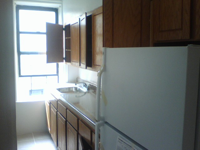 A pic of an empty kitchen with heinous oak cabinets