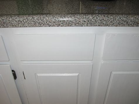 A detail shot of painted lower cabinet next to 'granite' countertop