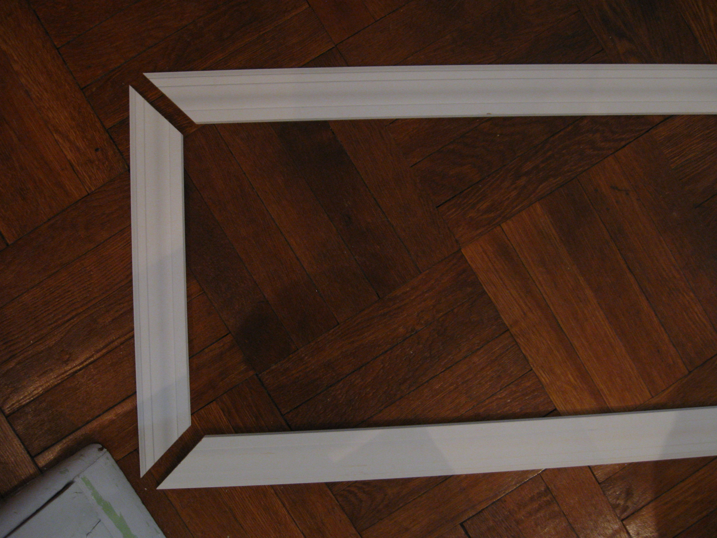 White wooden moulding that will frame bulletin board