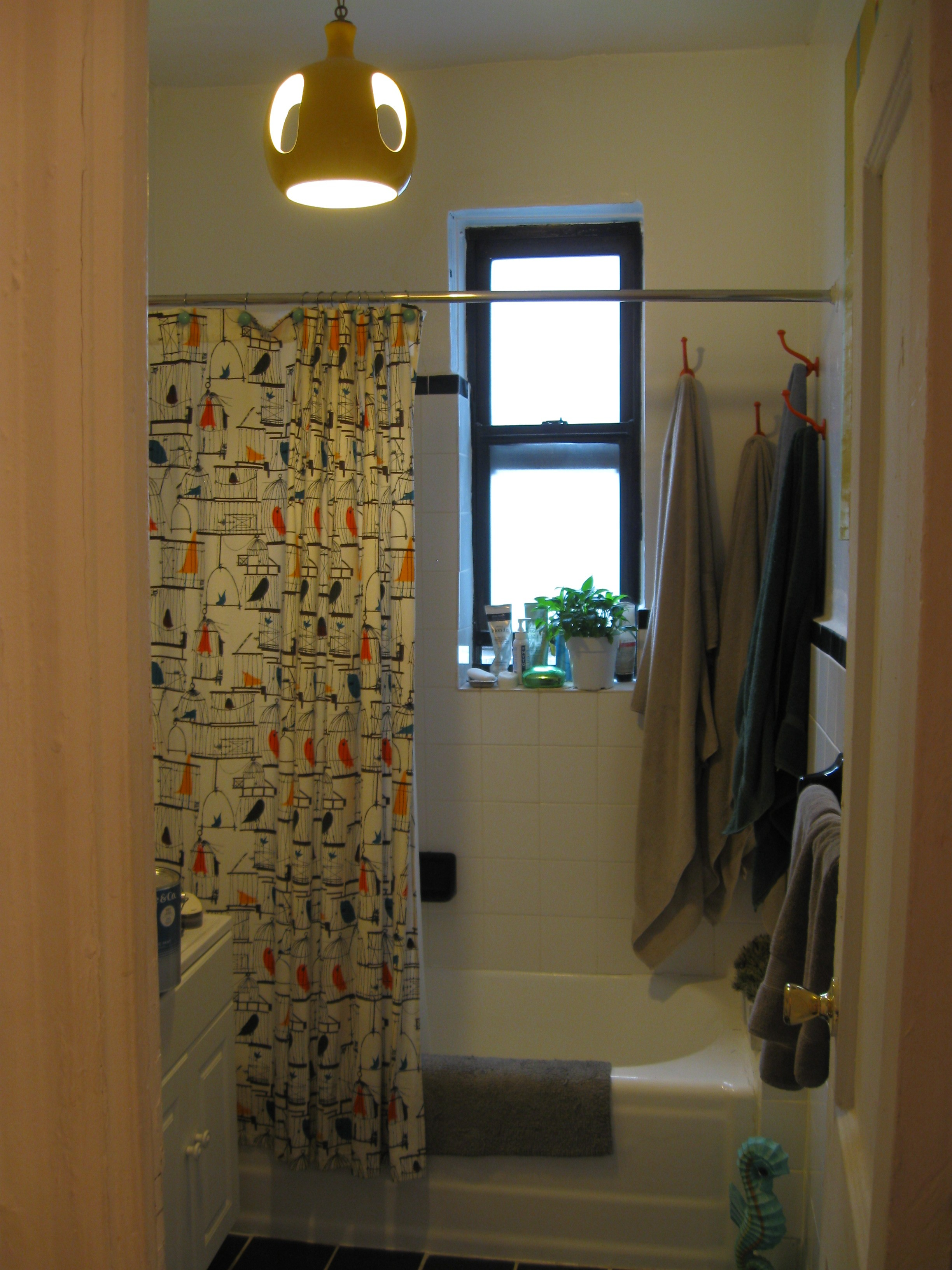 A photo of bathroom wall that will be painted in a fun pattern seen in shower curtain