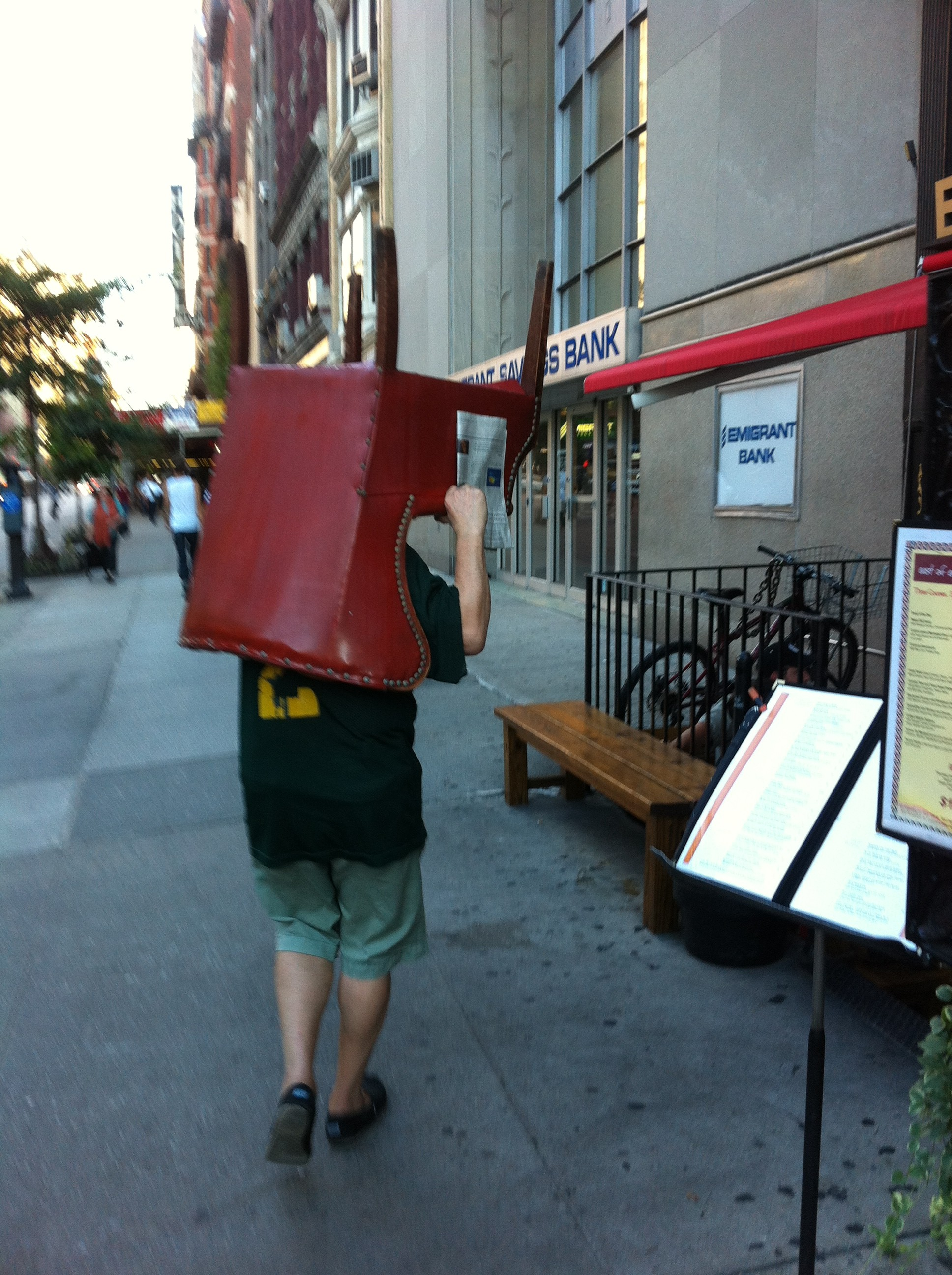 Man with a chair for a head strolling along 23rd street