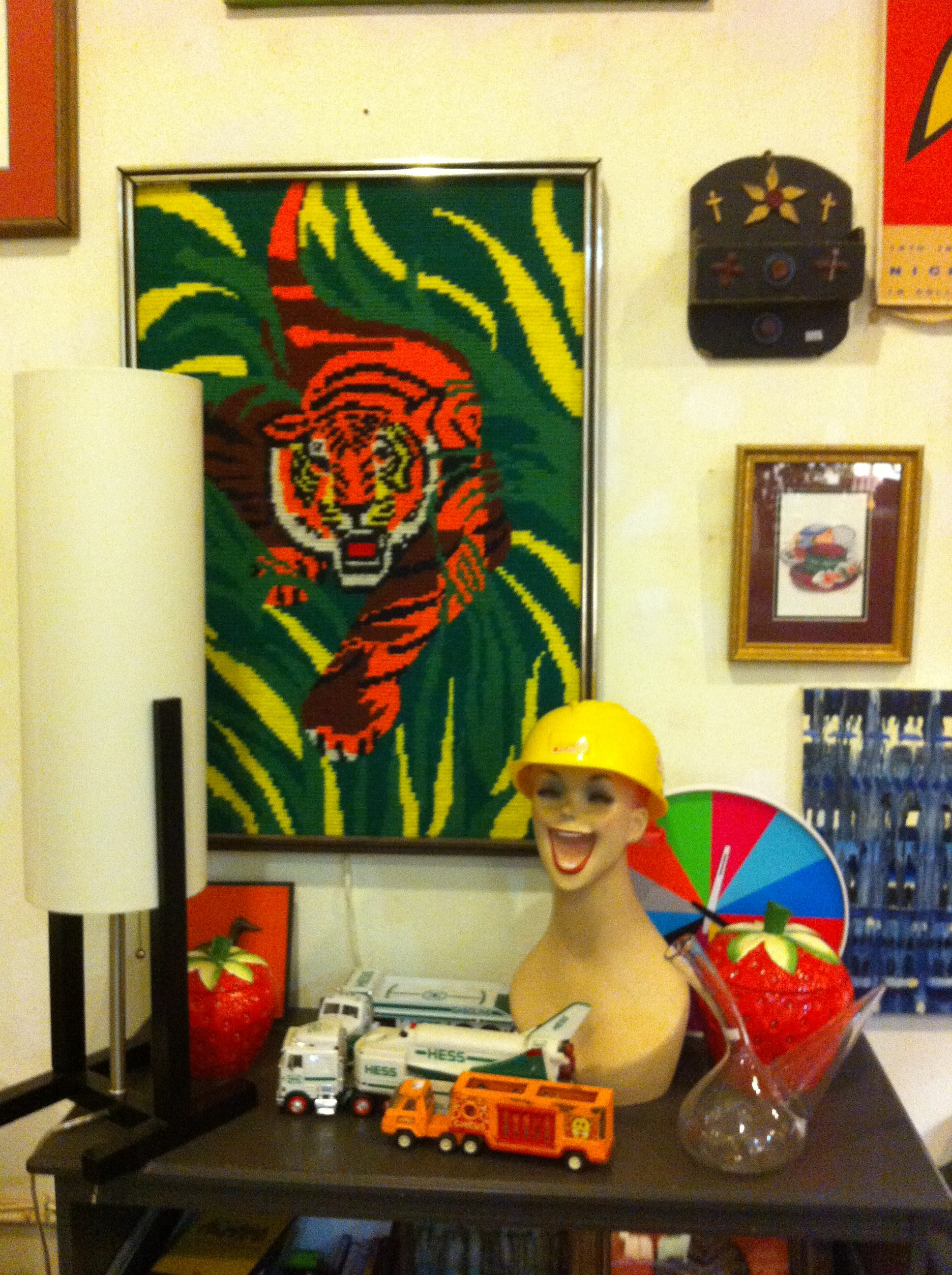 A yarn art tiger and smiley faced mannequin with hat