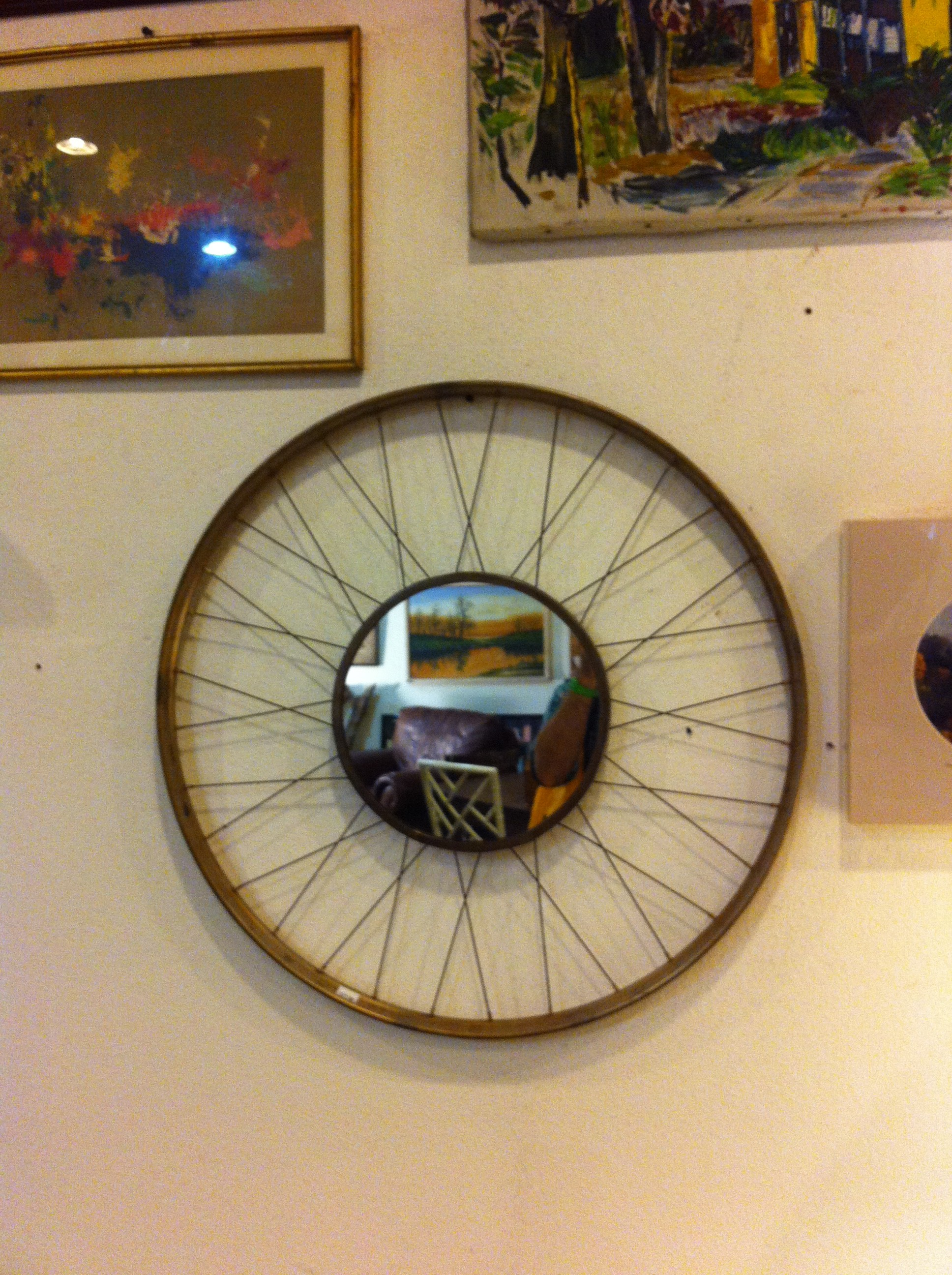 A pic of a bike rim turned into a mirror hanging on a wall