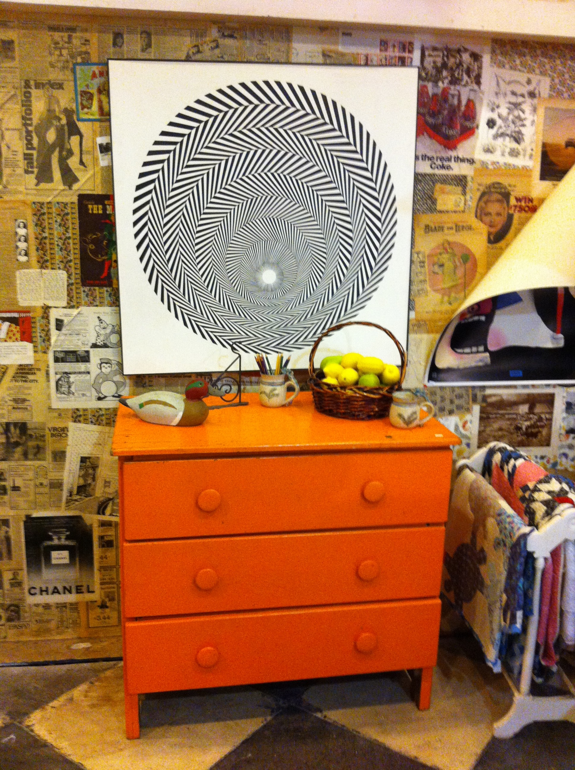 Pic of an orange dresser and abstract art above it