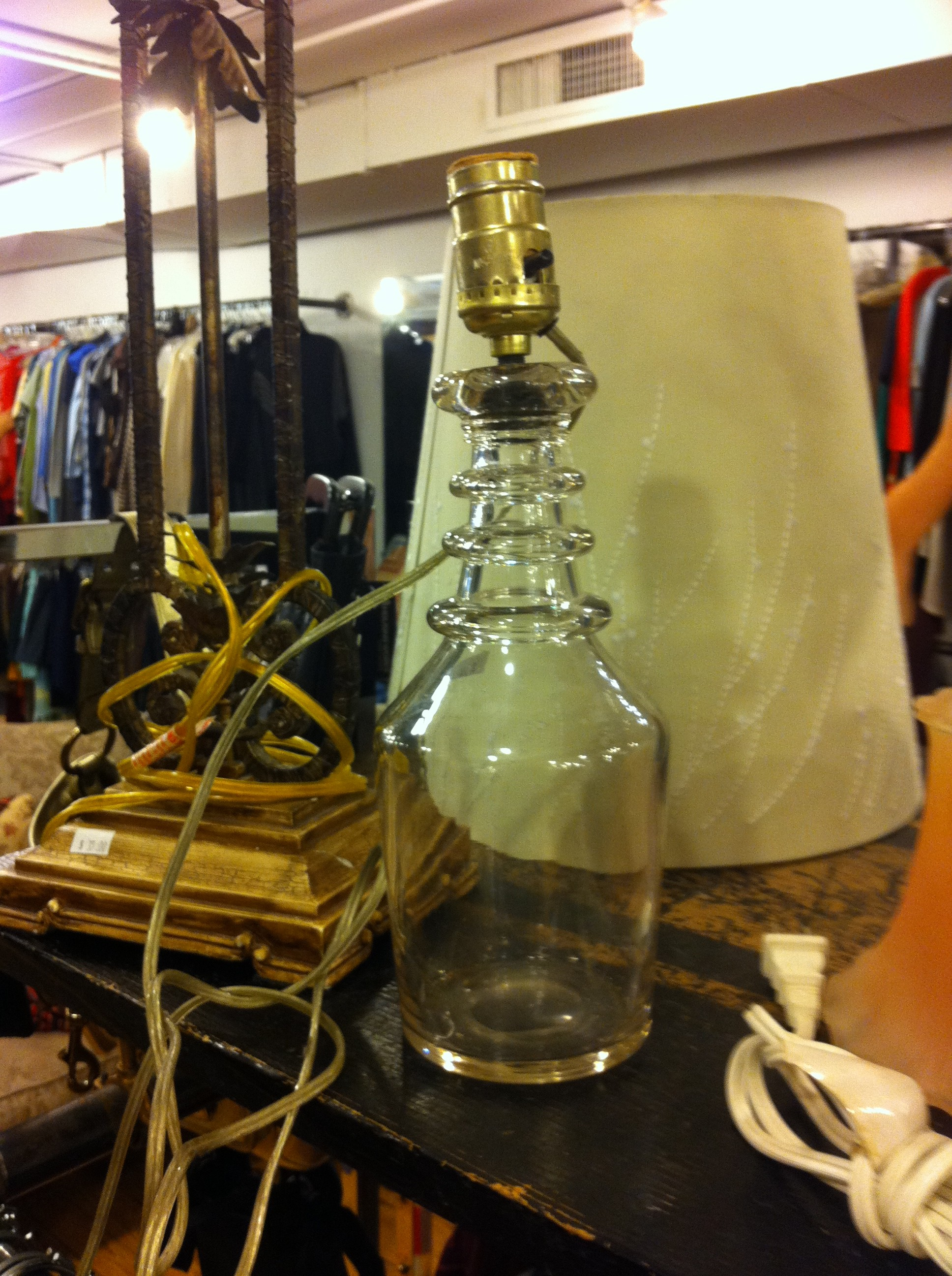 A pic of a clear glass small lamp in thrift shop