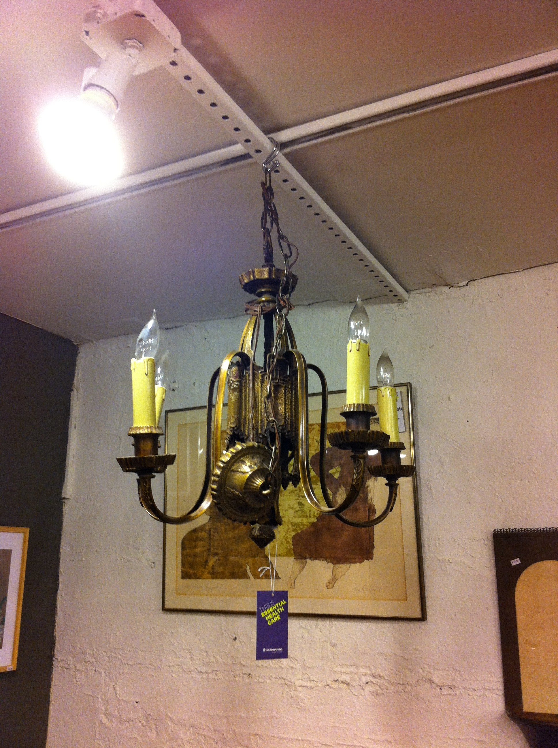 A pic of a bronze chandelier in thrift shop