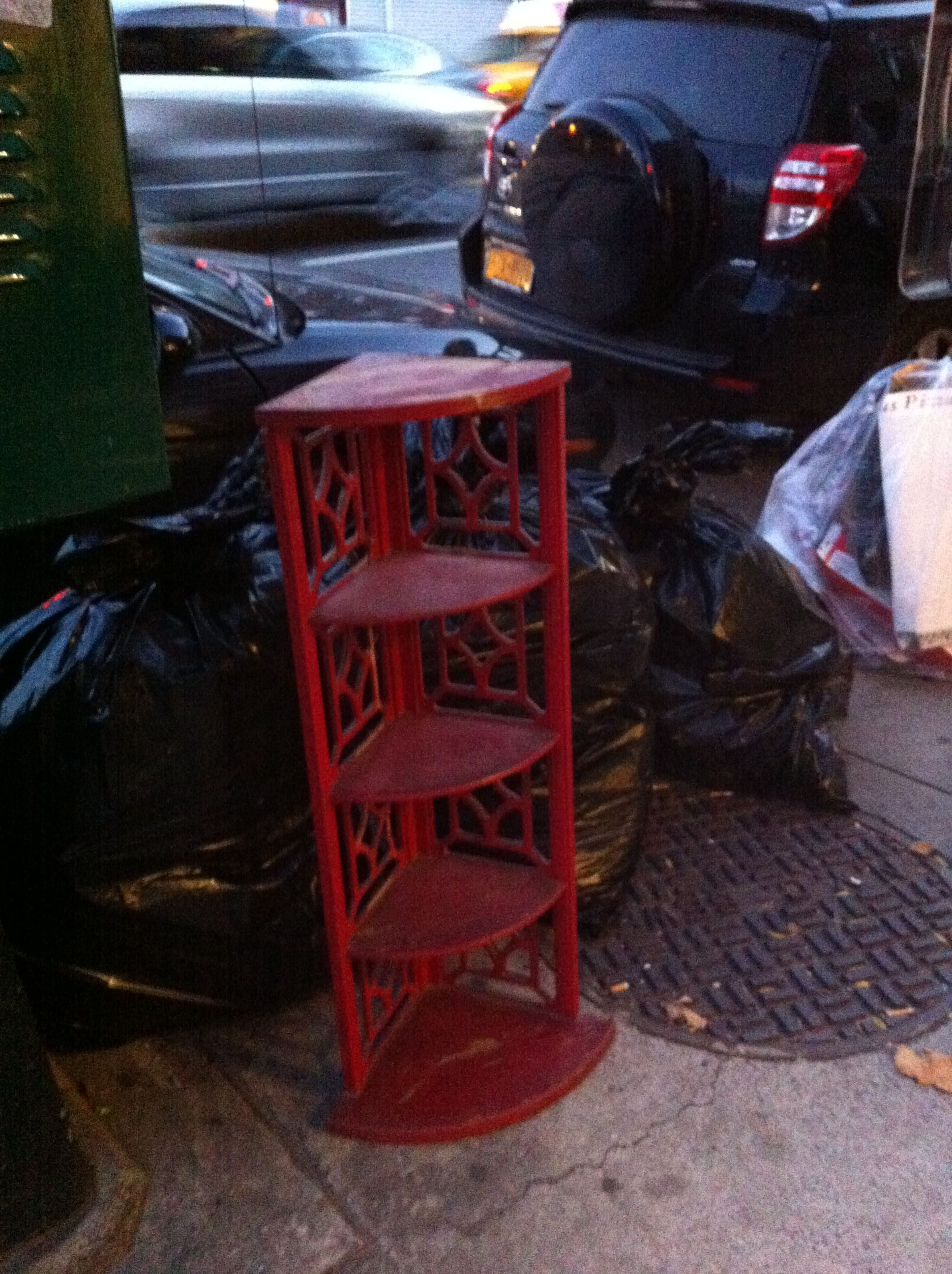 A pic of a red corner shelf unit off NYC street