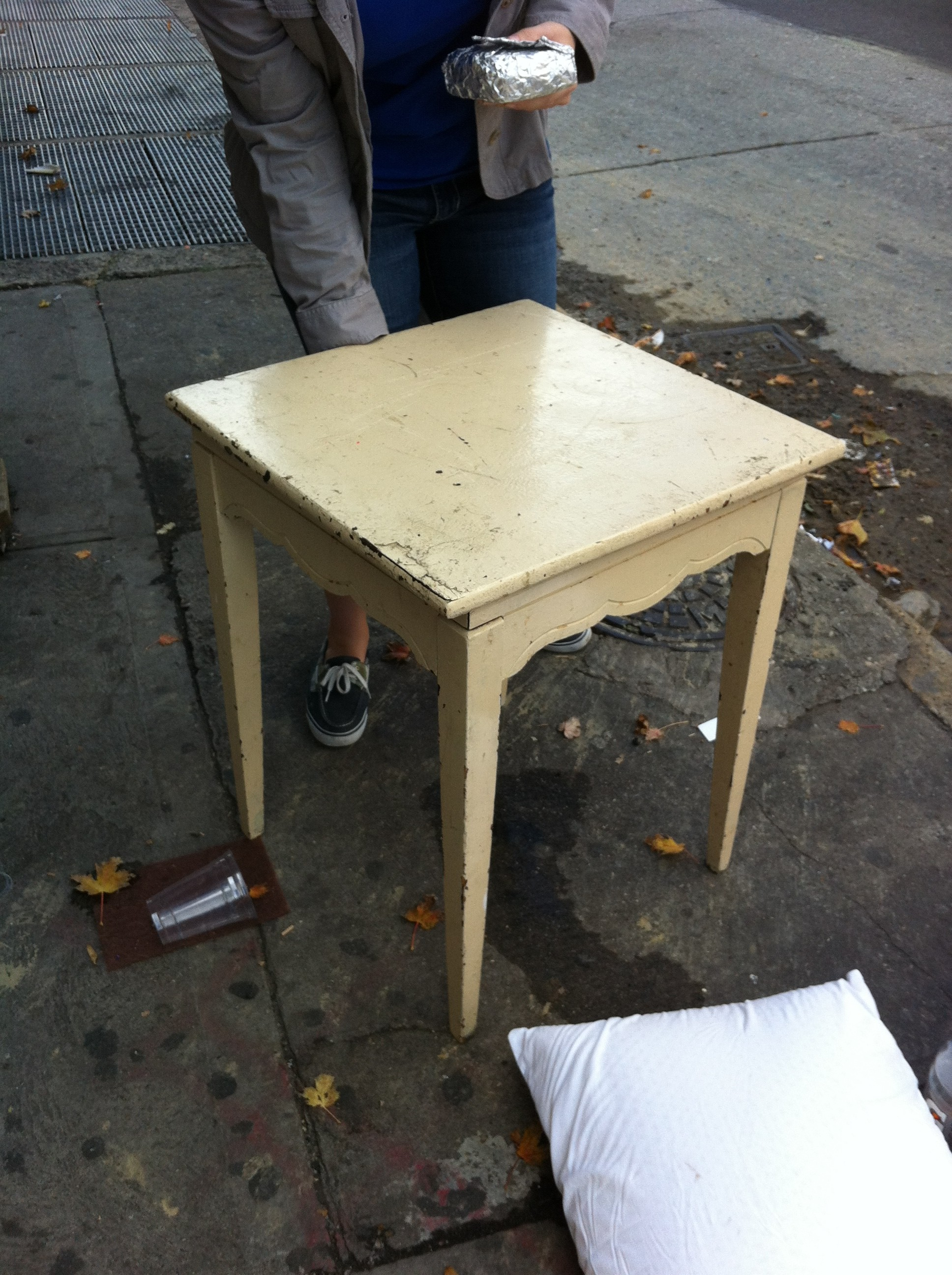A pic of a wooden side table left out on the curb