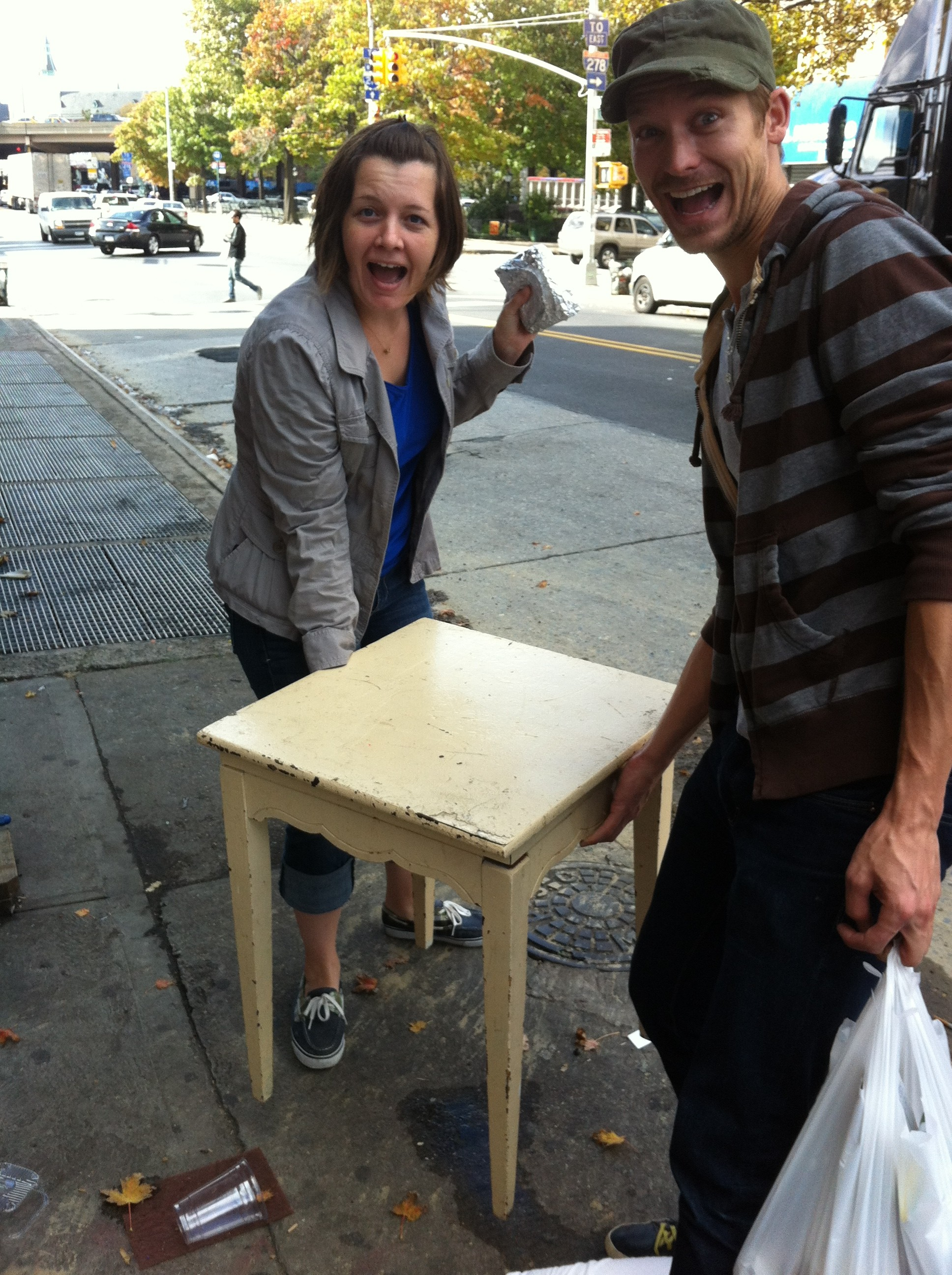 A close up of Debbie Wheatley and Chris White carrying a street find side table