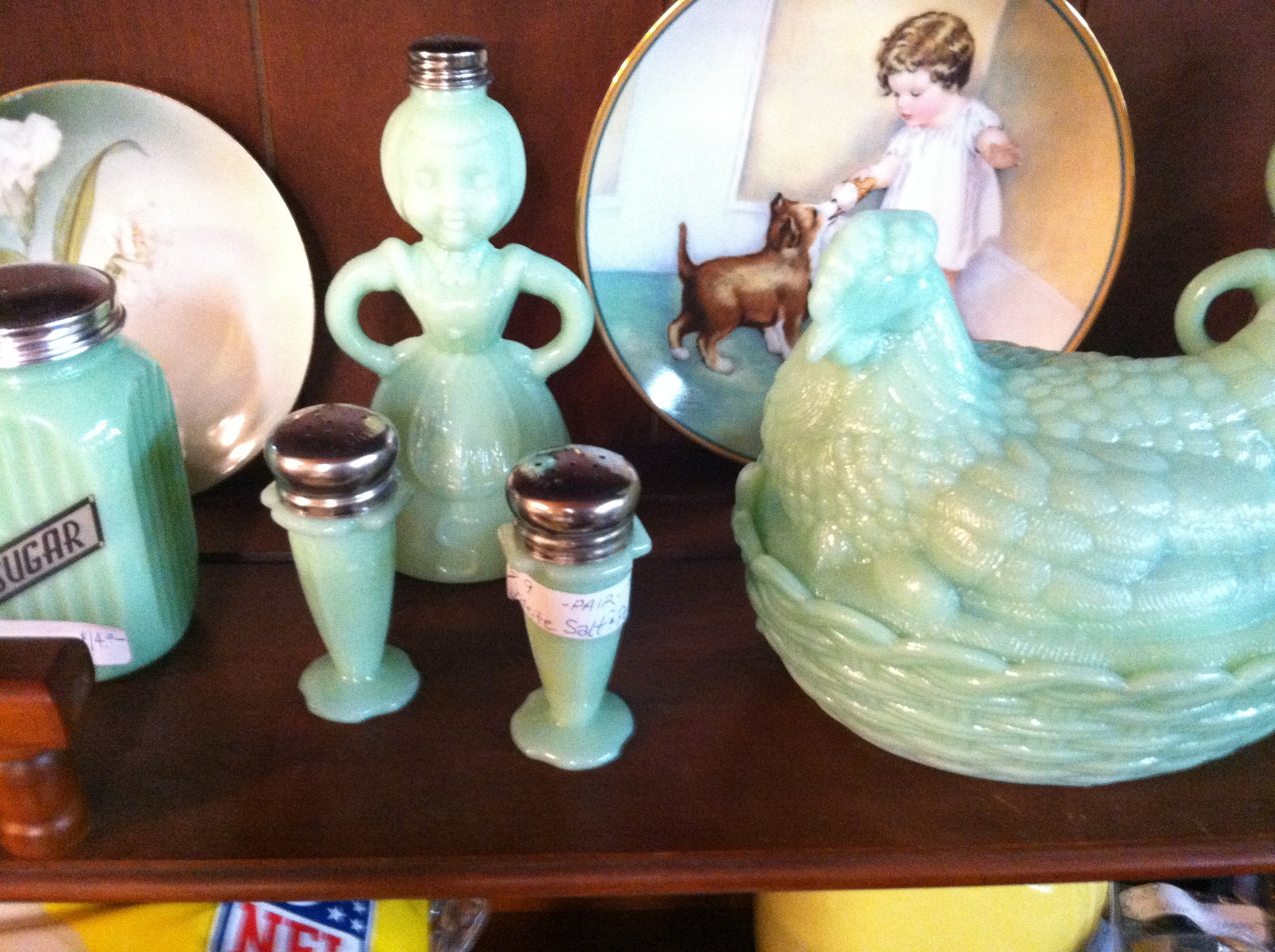 A tight shot of vintage jadeite syrup and salt and pepper shakers in thrift store