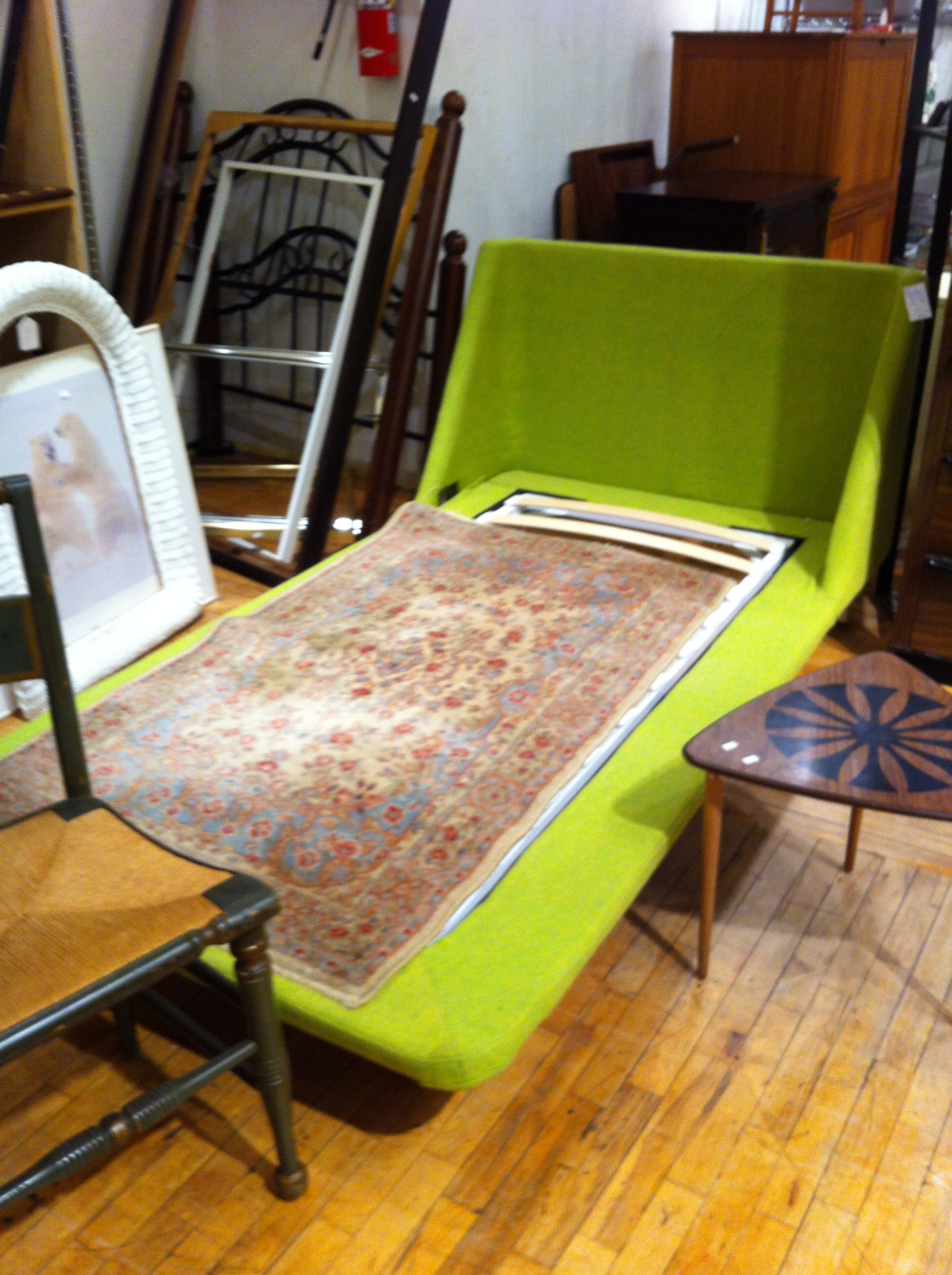 A pic of a green upholstered mid-century twin bed at Angel Street