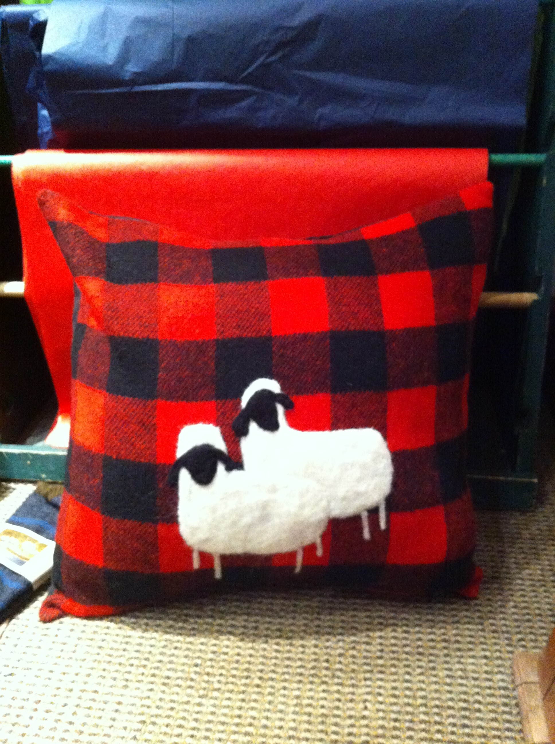 Red plaid pillow with two lambs embroidered on it