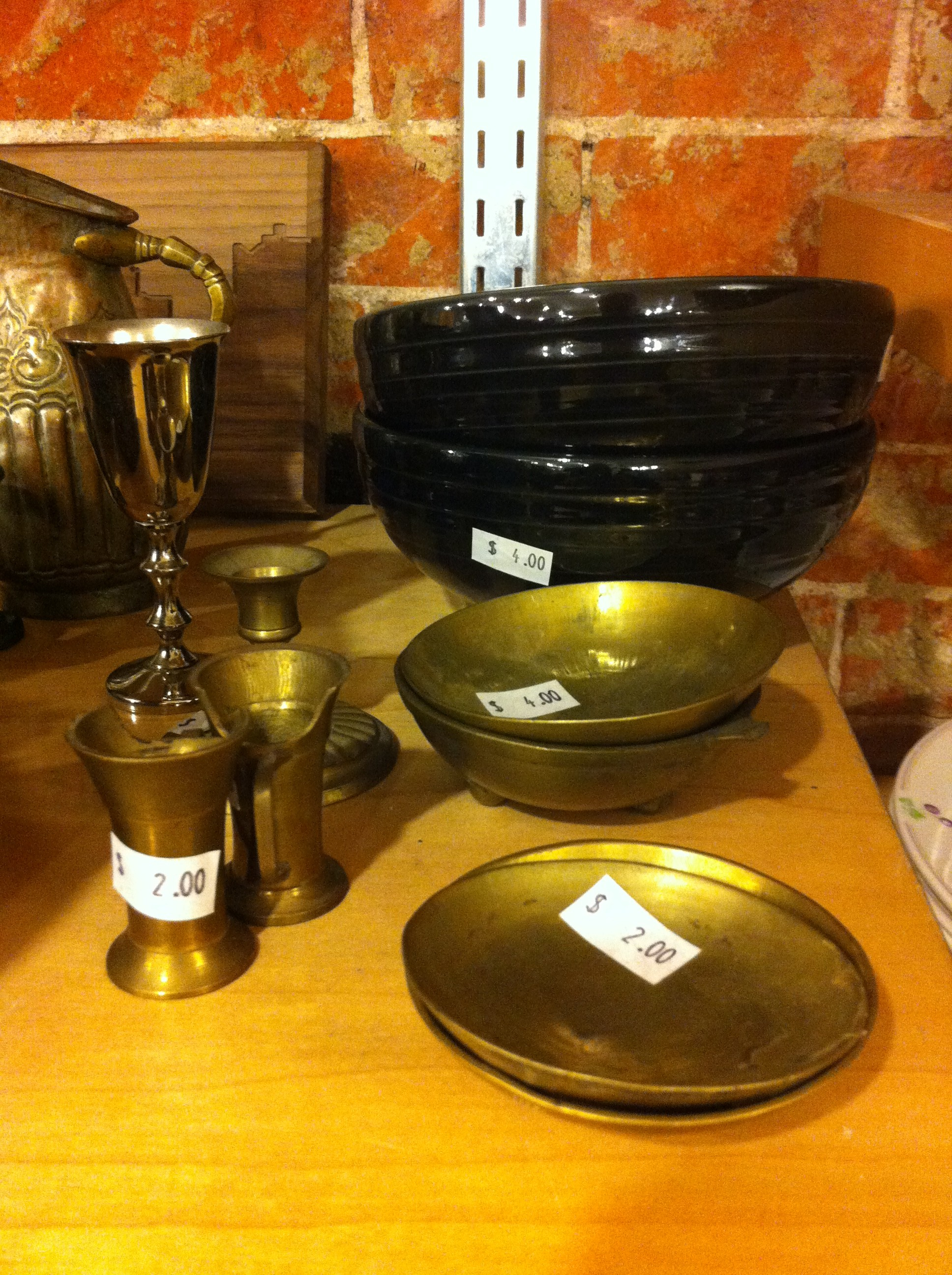 A pic of brass pinch bowls and shot glasses at thrift store