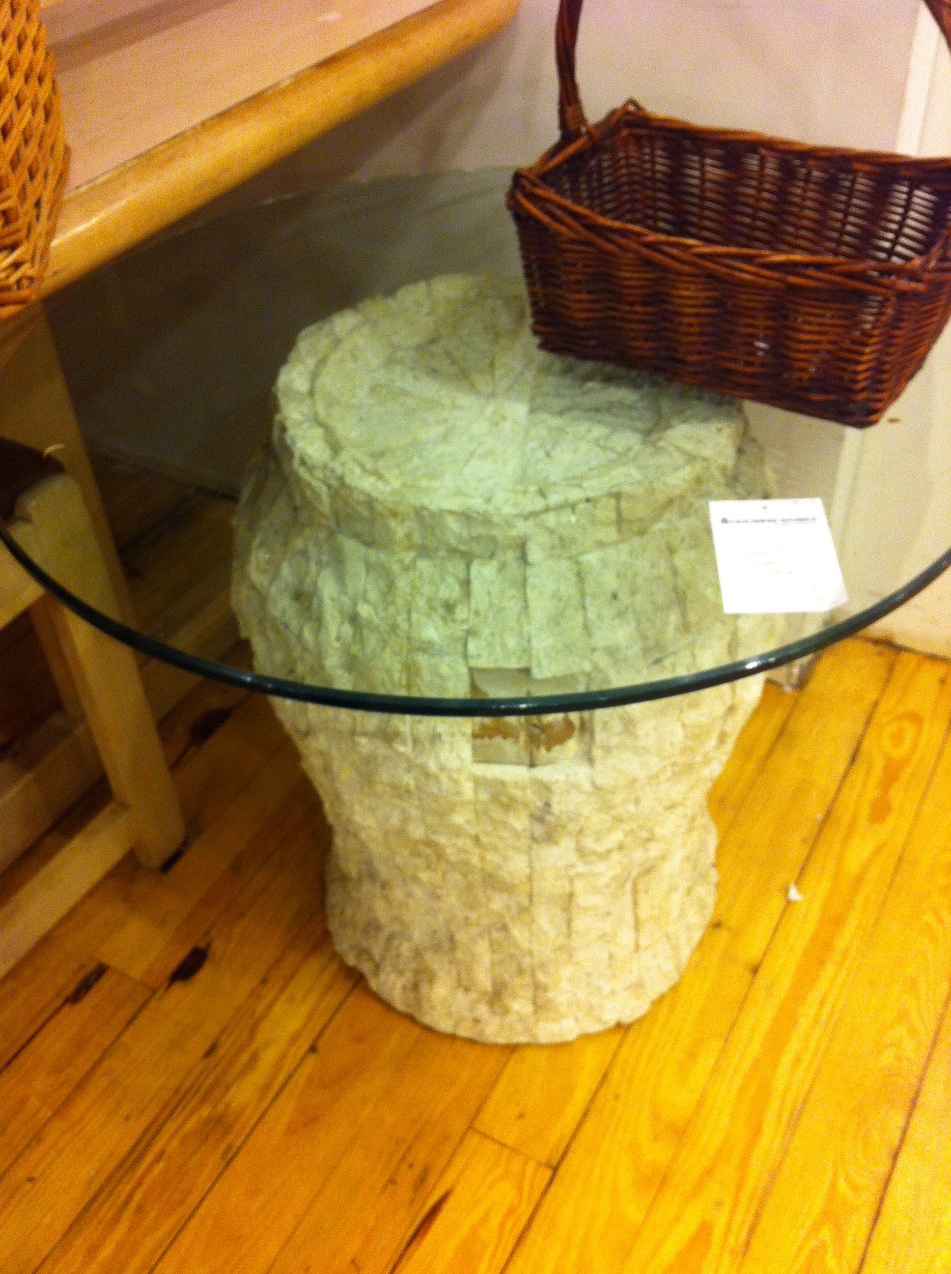 A pic of a side table with stone base and glass top