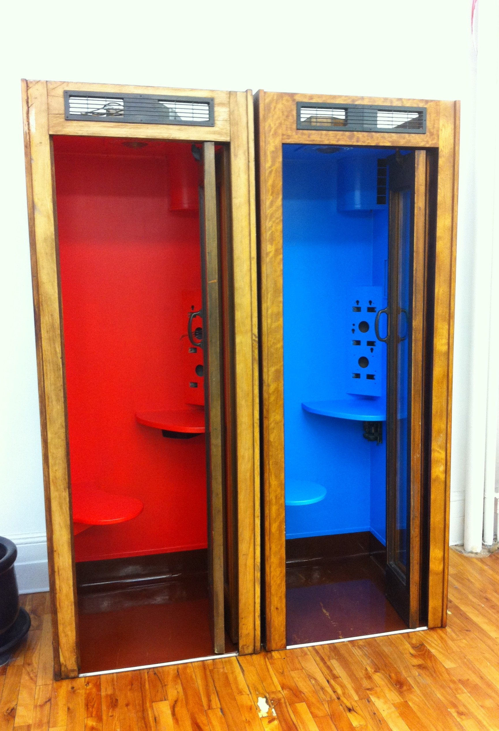 An AFTER shot of two vintage phone booths painted out in red and blue