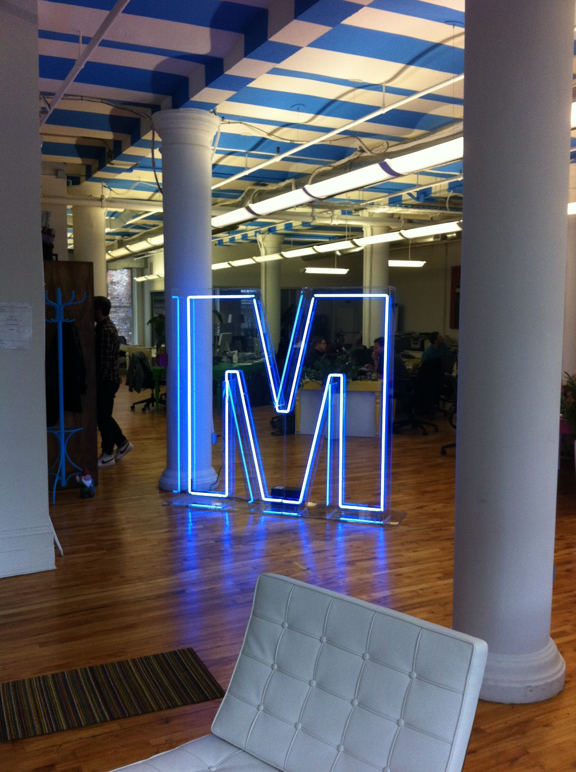 M neon logo sign at entryway to office