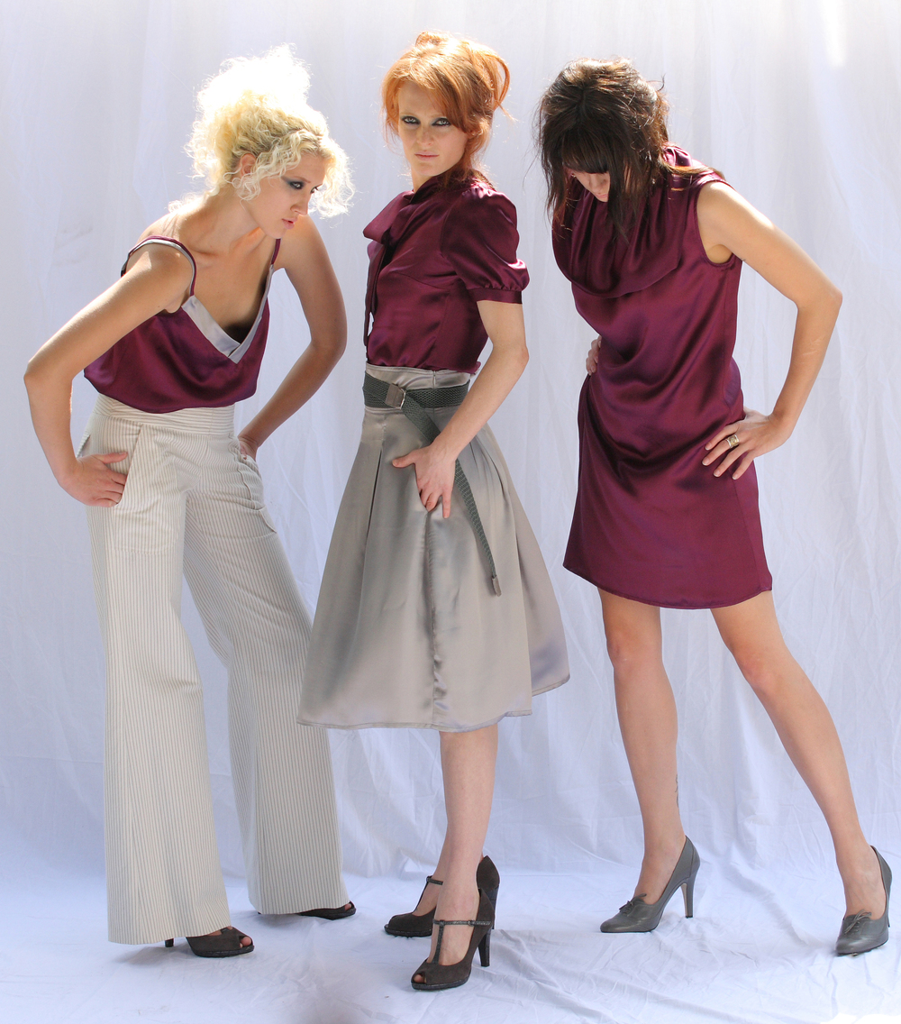 F  rom left to right:    Double Strap V-Cami in Plum Silk Charmeuse  Quilt Waist Wide Leg G.A Pant in Pinstriped Cotton Twill  Scarf Tied Blouse in Plum Silk Charmeuse. High Waist Pleat Skirt in Silver Silk Charmeuse. Extra Long Web Belt   Collar Sheath Dress in Plum Silk Charmeuse