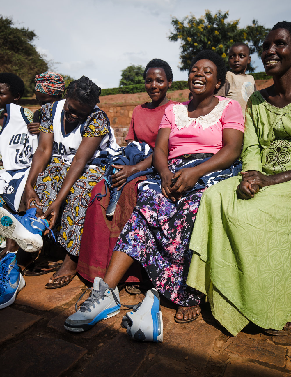 Some of the women on team Rwinkwavu receive basketball shoes from the NGO, Shooting Touch.