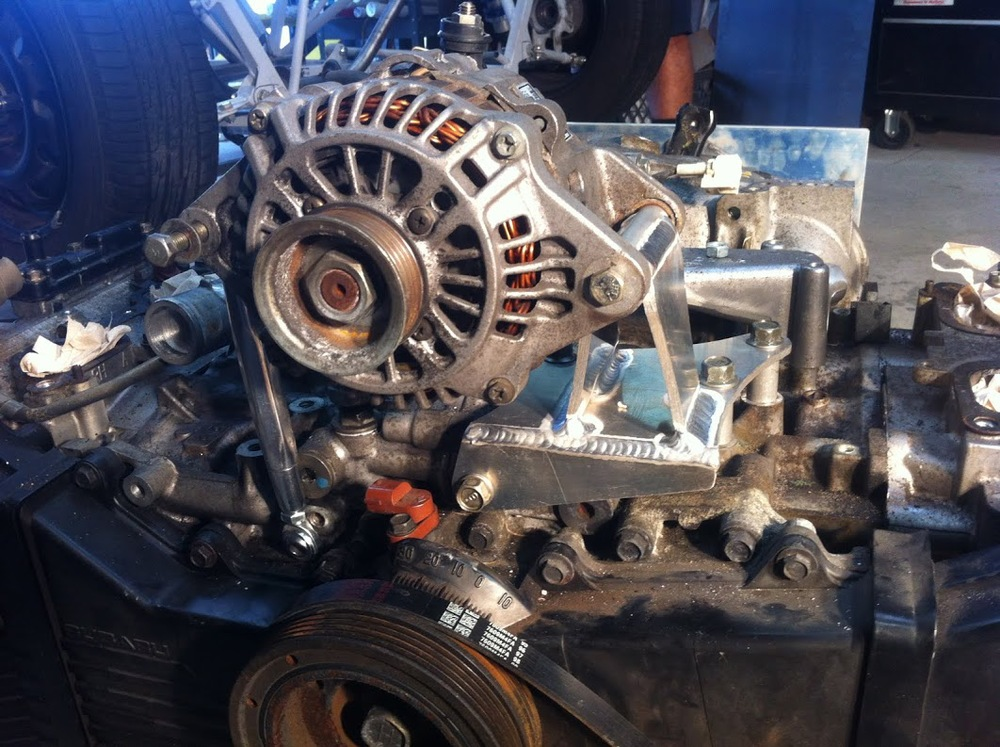 Alternator installed on motor with turnbuckle adjuster.