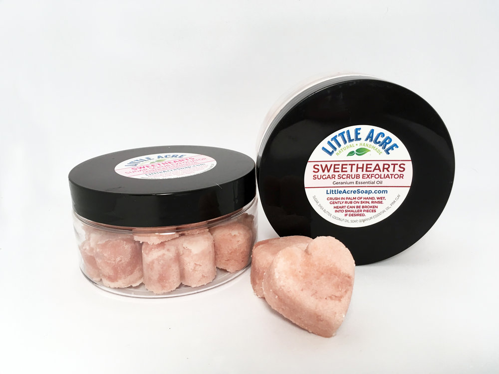SWEETHEARTS SOLID SUGAR SCRUB     Cute, heart-shaped scrubs scented with Geranium essential oil. Break off a corner to exfoliate face, or use the entire heart in the shower to exfoliate other body parts. Much more hygienic than a tub of traditional sugar scrub! There are 11 hearts in each jar. Made with Shea Butter for extra moisturizing benefits. Makes a great gift!       $10