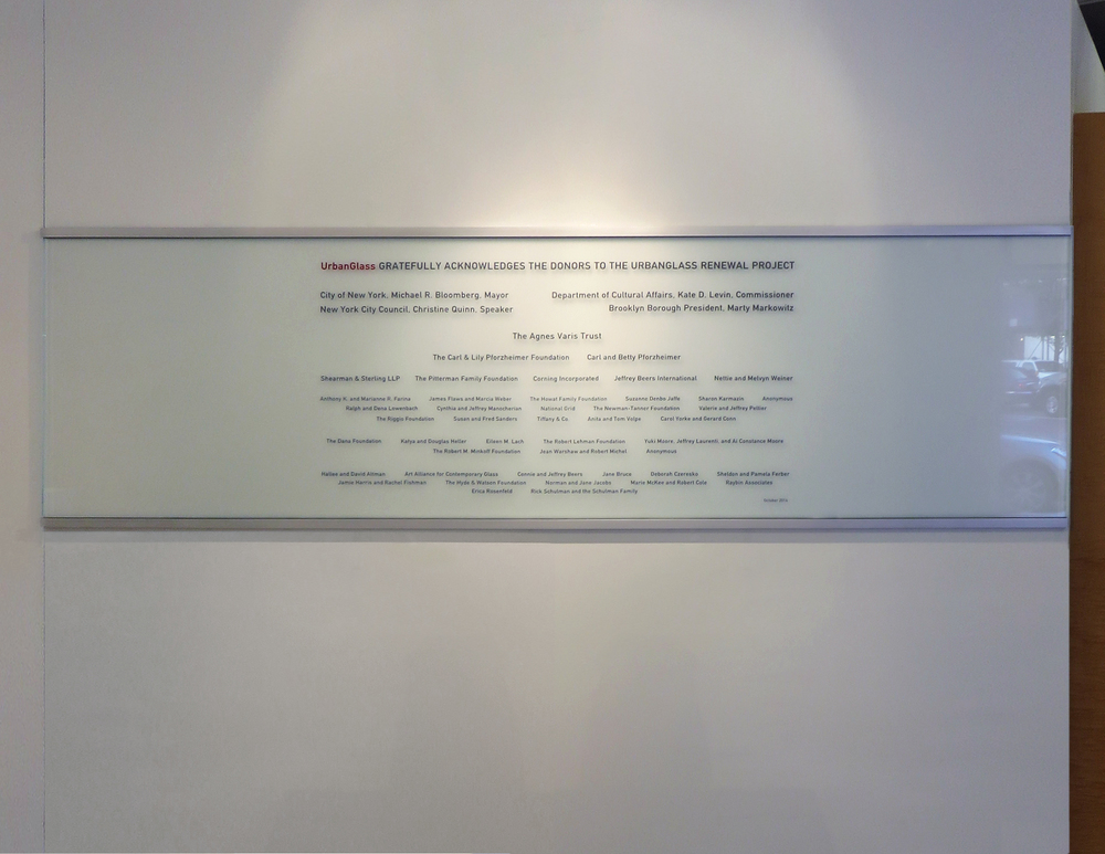 Custom sandblasted glass donor wall with carved and infilled text and gradient frosted etch finish.
