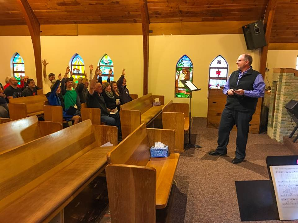 Pastor Mark had a stunned look on his face when every hand went up for Thanksgiving & Prayer. Something was up... That's when the flash mob stood and everyone began singing.
