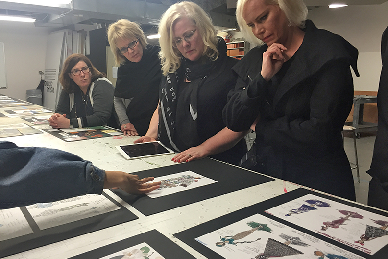 The Macy's Visual Team reviewing student drawings.