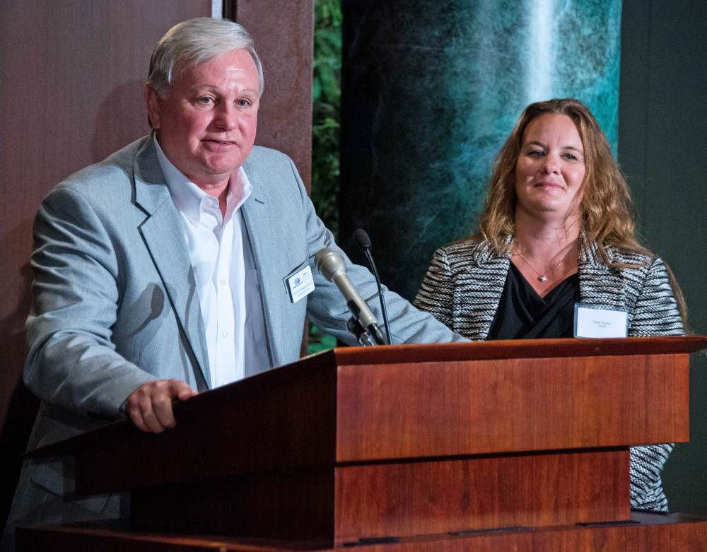 Rear Admiral (ret) Dan Kloeppel, CEO of CASY, speaking at the podium with Stacy Bayton, Chief Operating Officer, CASY