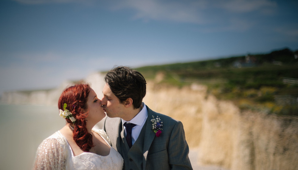 Married Couple Sharing KIss on Beach - Wedding Photographer