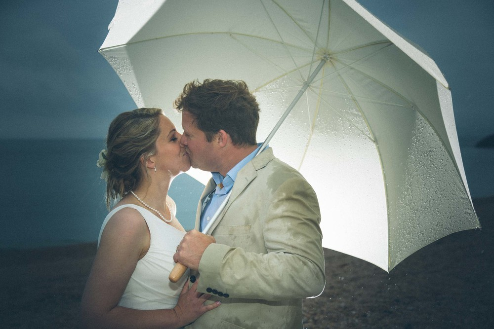 Married Couple Kissing Under Umbrella