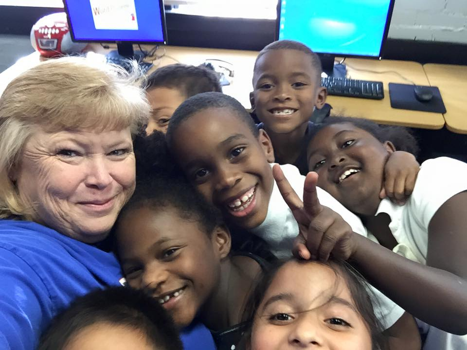 Math lab teacher, Mrs. Tracy, takes a break to pose for a selfie with her 2nd grade students