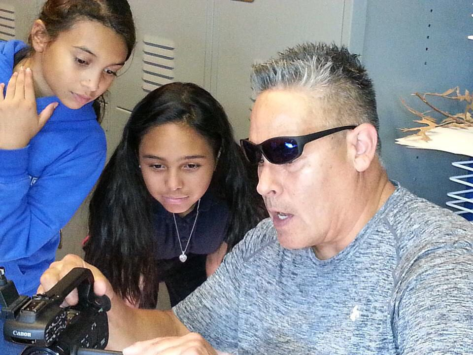 Volunteer Mr. Rick shows Tapanga and Aryana how to change the settings on the video camera