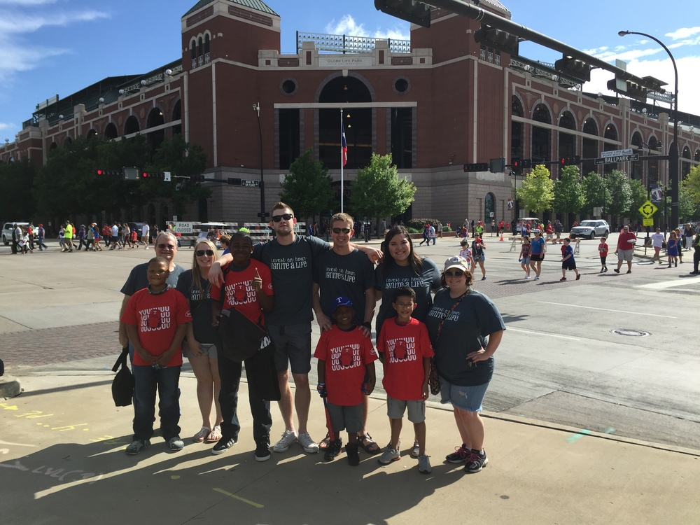 Four students saved enough money to go to a Ranger's game. They even got to invite their mentors to join them!