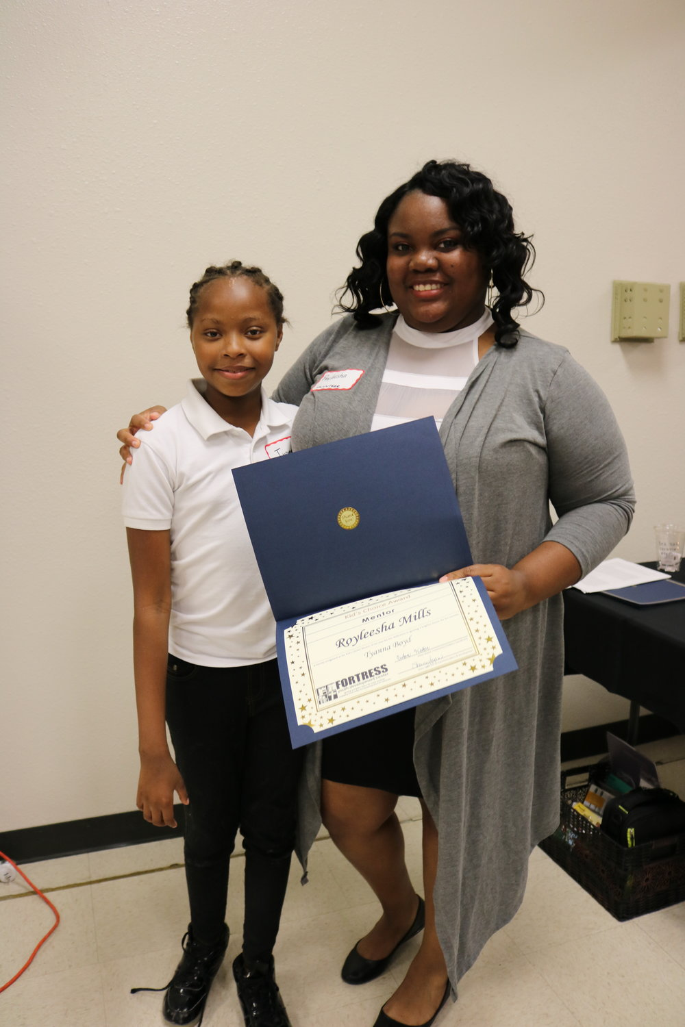 "Tyanna presents her mentor (who grew up at Fortress herself!) with the ""Kid's Choice Award"" at the 2018 Volunteer Appreciation Dinner. Tyanna nominated her mentor and wrote an essay about why she deserved to win!"