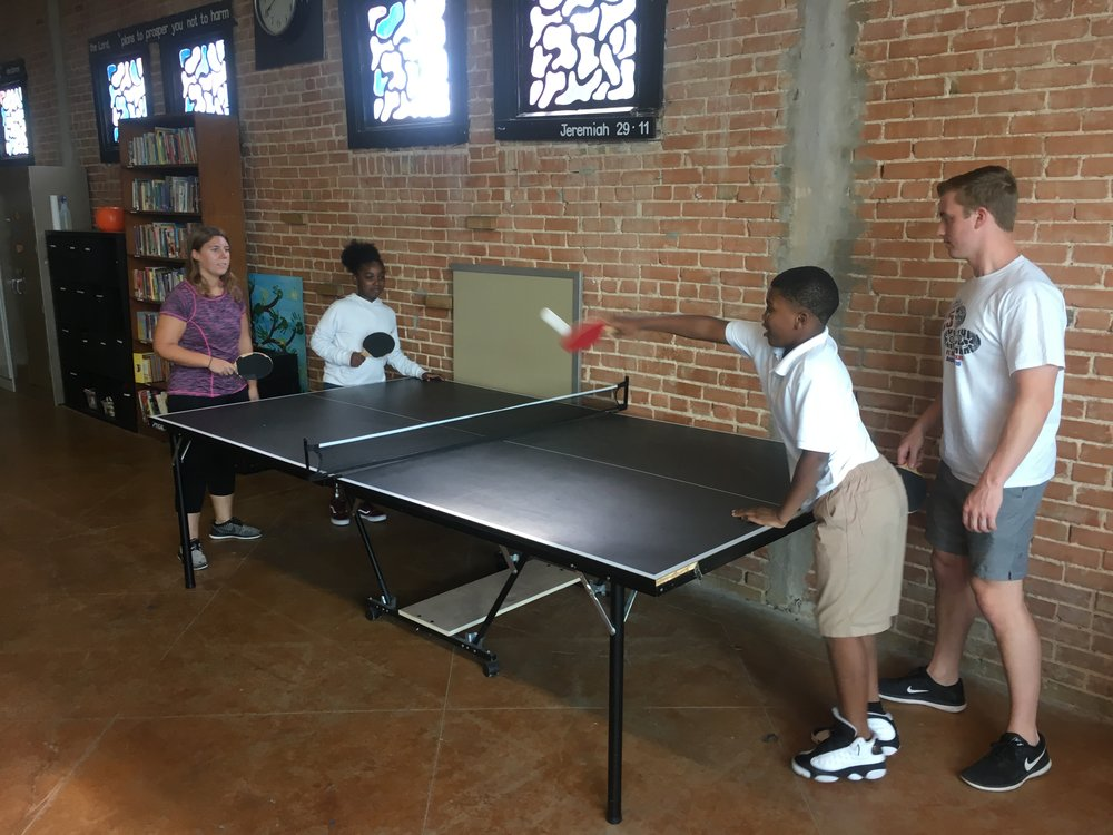 Two mentor-mentee pairs play doubles on the ping pong table.