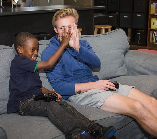 Amari and his mentor enjoy a video game together.