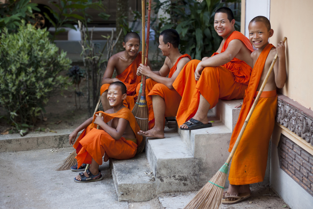 A few young monks from the monestary near the old airport park, take a break in between doing their chores.
