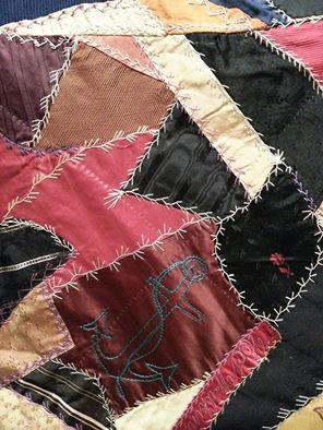 A close-up of the Wilkinson family Crazy Quilt, showing the stitching and the anchor.