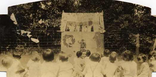 Children watch a puppet show at Guggenheimer-Milliken in 1930.