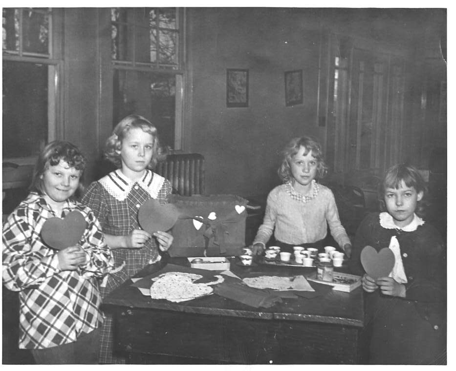 Four girls display their handmade Valentines, made at the Guggenheimer-Milliken community center in 1950.