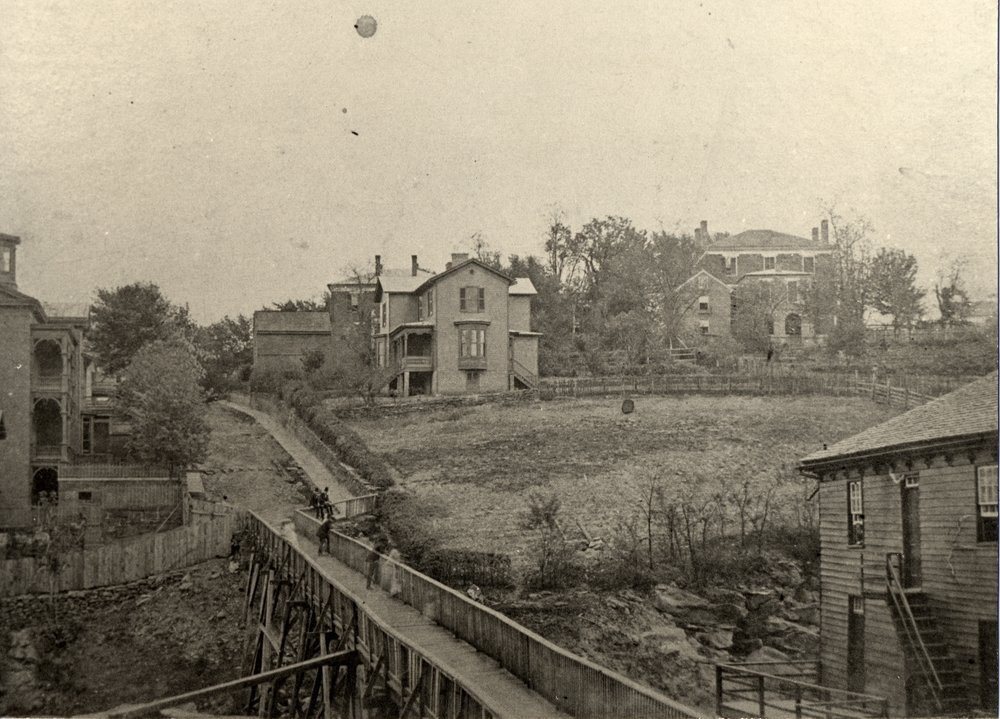 Church Street between 12th and 13th Streets looking towards Washington Street, ca. 1870. The footbridge seen here provided the only direct access to downtown from Washington Street from 1856-1870. The City Armory is located along this section of Church Street today.